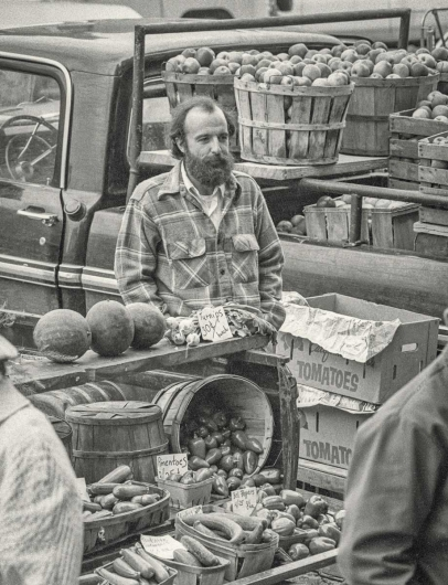 man selling vegetables at farmers market