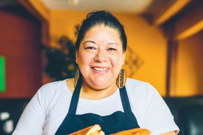 Maria Medina shows off her Torta Chilanga gigante cubana style, which is a giant sandwich with leg meat, chorizo, hot dogs, eggs, ham, and milanesa (a flattened steak that has been breaded and fried), all topped with cheese