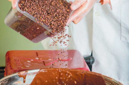 pouring cacao nibs into melted chocolate pot