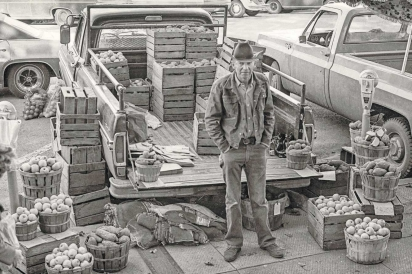 man sells apple from the back of his truck at farmers market
