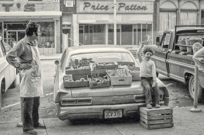 boy and his dad selling fruit and vegetables on trunk of pontiac car