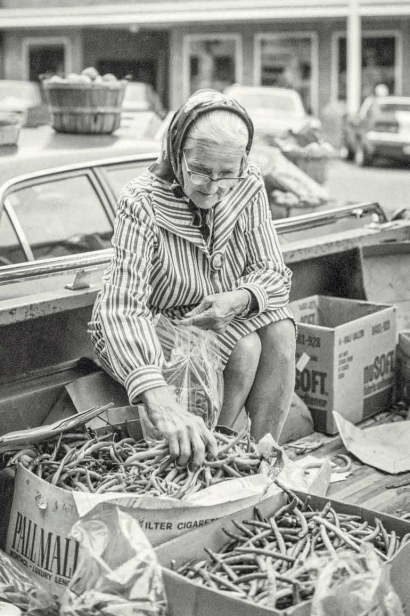 old woman sells green beans at farmers market