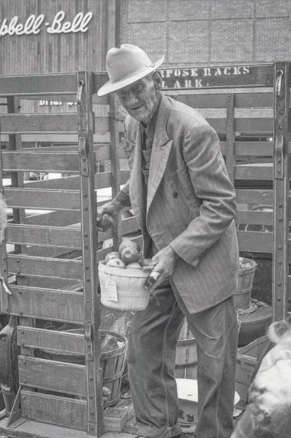 man holding basket of apples