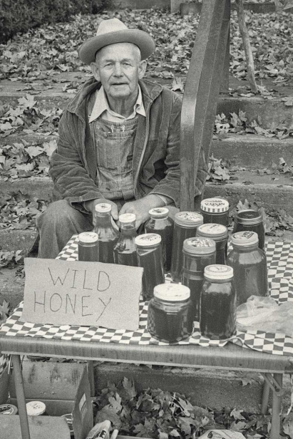 man sells wild honey on table outside